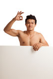 Muscular Asian man show OK  behind  blank sign Royalty Free Stock Photos