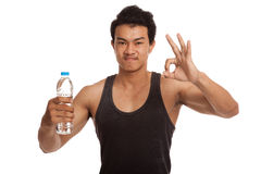 Muscular Asian man show OK with bottle of water Royalty Free Stock Images