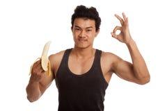 Muscular Asian man show ok with peeled  banana Royalty Free Stock Photos