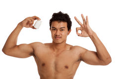Muscular Asian man show OK with white drug pill bottle. Isolated on white background Royalty Free Stock Photo