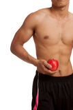 Muscular Asian man show six pack abs with red apple Royalty Free Stock Photo