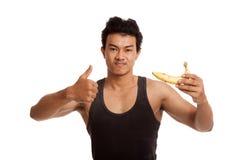 Muscular Asian man thumbs up with banana Stock Photo