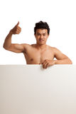 Muscular Asian man thumbs up  behind  blank sign Royalty Free Stock Photo
