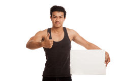 Muscular Asian man thumbs up with blank sign Stock Photo