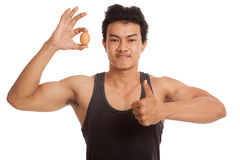 Muscular Asian man thumbs up with egg Stock Photo