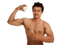 Muscular Asian man thumbs up with white drug pill bottle. Isolated on white background Royalty Free Stock Photography