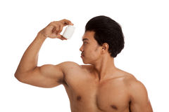 Muscular Asian man with white drug pill bottle. Isolated on white background Royalty Free Stock Photos