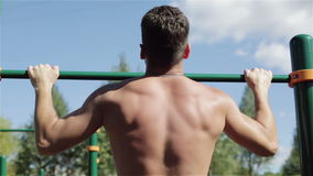 Muscular athlete back on the horizontal bar. Man pulling up outdoors. The blue sky and green trees on the background. View from back stock video footage