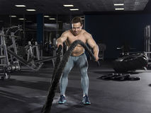 Muscular athlete with battle ropes exercise in modern fitness ce stock photography