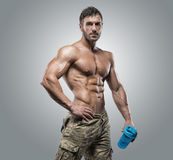 Muscular athlete bodybuilder man on a gray background. Muscular athlete bodybuilder man in camouflage pants with a naked torso on a gray background Stock Images