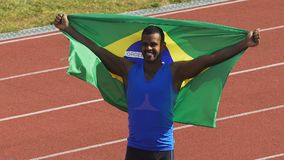 Muscular athlete of Brazilian national team celebrating victory showing his flag