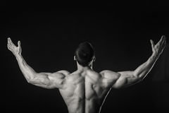 Muscular athlete demonstrates his muscles under load on a dark background Stock Photo