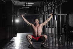 Muscular athlete doing the crossfit exerise in the gym.Doing the. Strong crossfit athlete in a heavy overhead squat lift in a cross-fit  gym.Snatch exercise Stock Photography