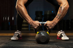 Muscular athlete doing exercise with kettlebell Stock Images