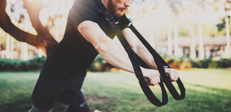 Muscular athlete exercising trx push up outside in sunny park. Fit shirtless male fitness model in crossfit exercise stock images