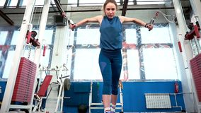 Muscular athlete girl engaged in lifting weights on the simulator.