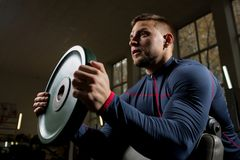 Exercise with disk. Muscular athlete holding heavy iron disk in front of him during weightlifting workout Royalty Free Stock Image