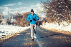 Muscular athlete man jogging outdoor on snow, training Royalty Free Stock Images