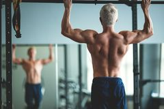 Muscular athlete man making Pull-up in gym. Bodybuilder training in fitness club showing his perfect back and shoulder. Muscles. Toned image Stock Photos