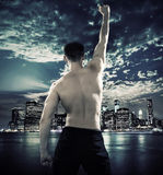 Muscular athlete over the city background Royalty Free Stock Photo