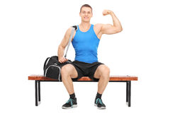 Muscular athlete showing his bicep seated on a bench Royalty Free Stock Photos