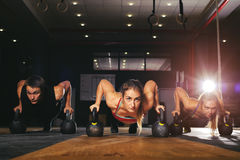 Muscular athletes doing push ups with kettlebell. Young muscular athletes doing push up exercise with kettlebell equipment. Weightlifting, power lifting workout Stock Image