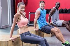 Muscular athletes doing reverse push up. Portrait of three muscular athletes doing reverse push up royalty free stock photos
