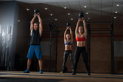 Muscular athletes exercising with kettle bell stock photos