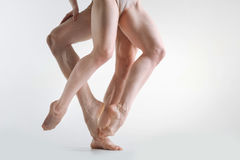 Muscular athletes legs dancing in the white colored studio. Professional sport in details . Sculptural tensed graceful athletes legs standing in the white Royalty Free Stock Image