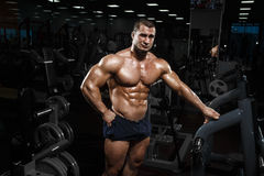 Muscular athletic bodybuilder fitness model posing after exercises in gym royalty free stock photo