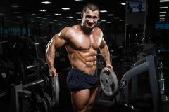 Muscular athletic bodybuilder fitness model posing after exercises in gym stock photos