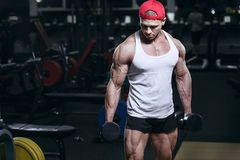 Muscular athletic bodybuilder fitness sport model workout in gym stock photography