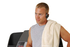 Muscular athletic man leaning on a treadmill Stock Images