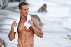 Muscular athletic sexy man in white pants with a naked torso on the beach. Portrait of tanned fit male model on vacation stock image