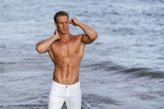 Muscular athletic sexy man in white pants with a naked torso on the beach. Portrait of tanned fit male model on vacation royalty free stock images