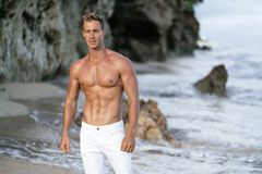 Muscular athletic sexy man in white pants with a naked torso on the beach. Portrait of tanned fit male model on vacation stock images
