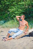 Muscular attractive man. Muscular attractive man resting on the beach Royalty Free Stock Photo