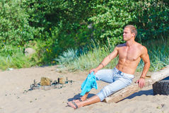 Muscular attractive man resting. Muscular attractive man resting on the beach Royalty Free Stock Photos