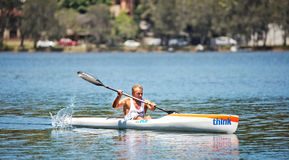 Muscular Aussie guy paddling a canoe Stock Images