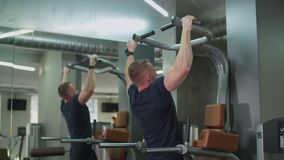 Muscular man performing pull-ups in fitness club