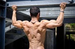 Muscular back of male bodybuilder hanging from metal structure Royalty Free Stock Photo