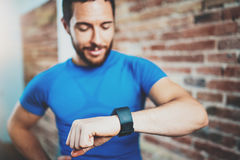 Muscular bearded athlete checking burned calories on electronic smart watch application after good workout outdoor Royalty Free Stock Image