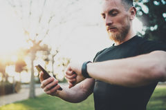 Muscular bearded athlete checking burned calories on smartphone application and smart watch after good workout session Royalty Free Stock Photography