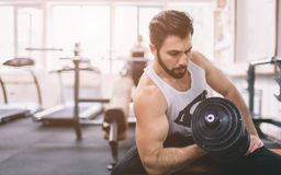 Muscular Bearded man during workout in the gym. Athlete muscular bodybuilder in the gym training biceps with dumbbell Royalty Free Stock Photography
