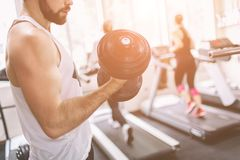 Muscular Bearded man during workout in the gym. Athlete muscular bodybuilder in the gym training biceps with dumbbell Royalty Free Stock Images