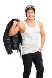Muscular biker holding a leather jacket Royalty Free Stock Photography