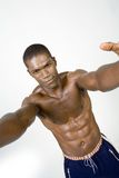 Muscular Black athlete. A studio view of a very well conditioned and muscular African American male athlete as he  reaches out with his arms Royalty Free Stock Image