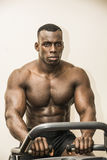 Muscular black bodybuilder exercising on stationary bike in gym. Hunky muscular black male bodybuilder exercising on stationary bike in gym, looking at camera Royalty Free Stock Photography