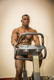 Muscular black bodybuilder exercising on stationary bike in gym. Hunky muscular black male bodybuilder exercising on stationary bike in gym, looking straight Stock Photo