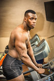 Muscular black male bodybuilder exercising on treadmill in gym Stock Image